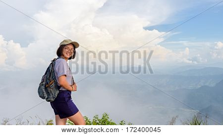 Teens girl hiker wear a cap and glasses with backpack is standing and smiling happily on high mountain at scenic point of Phu Chi Fa Forest Park in Chiang Rai Province Thailand 16:9 widescreen