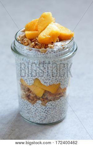 Chia pudding with peach and mango slices in a jar