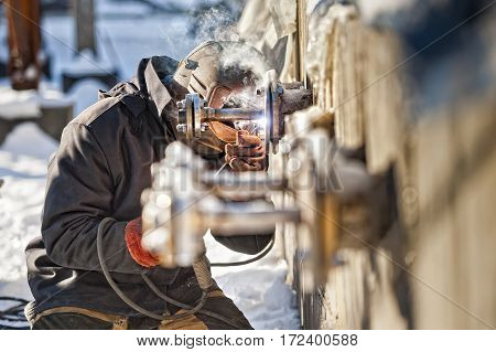 man in a helmet at work with construction tools welder