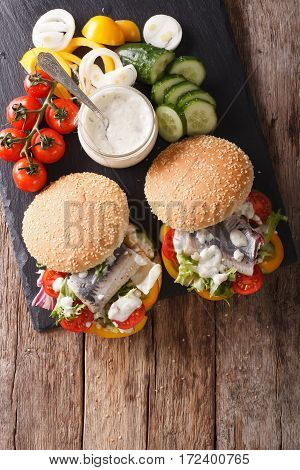 Fishburger With Herring, Gravy And Fresh Vegetables Close-up. Vertical Top View