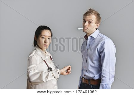 Portrait of a patient with thermometer in mouth standing with doctor