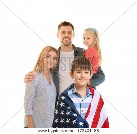 Cute boy wrapped in USA flag with family behind
