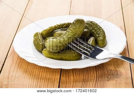White Plate With Gherkins And Cucumber On Fork