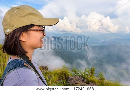 Hiker asian cute teens girl with caps and glasses smiling happily while looking beautiful landscape nature of mountain range and sky during sunset in winter at Phu Chi Fa Forest Park Chiang Rai Thailand
