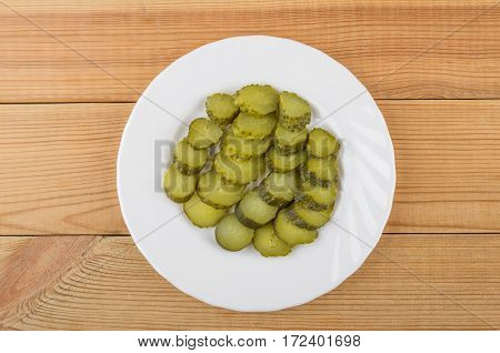 Slices Of Pickled Gherkins In White Plate On Wooden Table