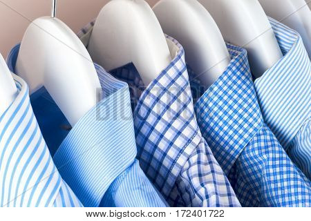 Clothes hang on a shelf . Cloth Hangers with Shirts. Men's business clothes