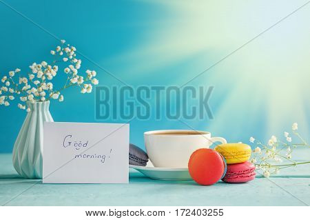 Cup of coffee or tea with wite flower and macaroons with blank on blue background.