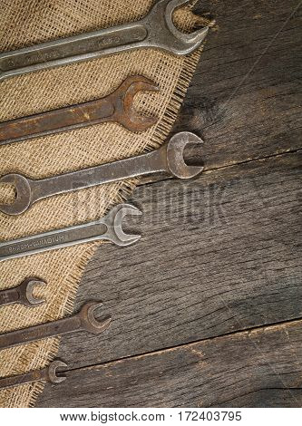 old and rusty spanners on a background of a wooden table and sacking. Space for text.