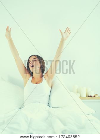 An attractive young woman stretching in bed after waking up.