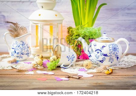Spring floral still life with hyacinth, hearts. Blue teapot, cup, moss. Lantern, feathers and quail eggs on wooden background