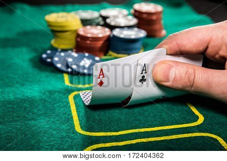 casino gambling poker people and entertainment concept - close up of poker player with playing cards and chips at green casino table