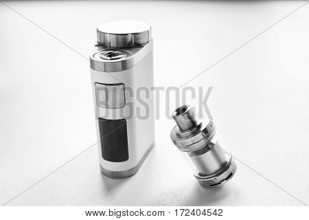 Electronic Cigarette And Liquid Tank On The Table. Vaping. Black And White  Ends.