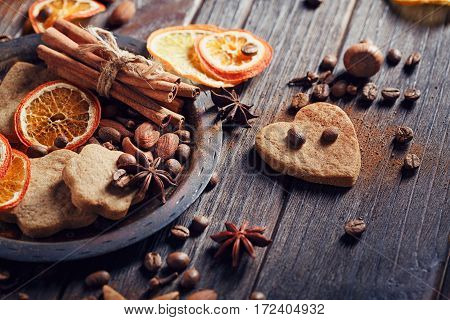 Homemade gingerbread cookies spices and decorations on wooden background. Seasonal holidays concept.
