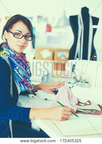 Young dressmaker designing clothes pattern on paper .