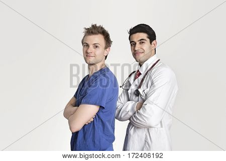 Portrait of a confident doctor and male nurse standing with arms crossed over gray background