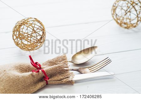 Rustic cutlery set: vintage knife fork and spoon on a white wooden background. Table with antique cutlery on the burlap with copy space close-up. Cutlery wrapped in burlap.