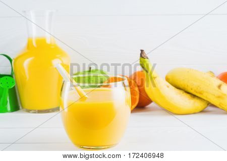 A glass of fresh orange juice and fruits orange tangerine apple banana on white wooden background with copy space. Healthy lifestyle and diet concept. Healthy eating for weight loss.
