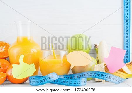 A glass of fresh orange juice and fruits orange tangerine apple banana and measuring tape on white wooden background with copy space. Diet concept. Healthy eating for weight loss.