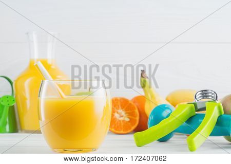 A glass of fresh orange juice and fruits tangerine apple banana dumbbell hand gripper on white wooden background. Healthy lifestyle and diet concept. Healthy eating for weight loss.