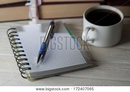Note Pad And Pen On A Table Littered With Books And Cup Of Coffee. Preservation Of Records.