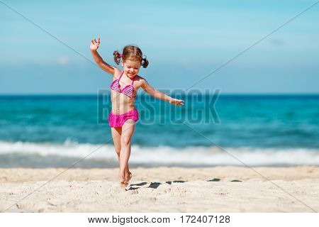 Happy child girl in bikini running on the beach in the summer sea
