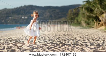 Happy child girl in a white dress running on the beach by the sea in summer