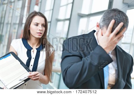 Defeated businessman turns away form coworker