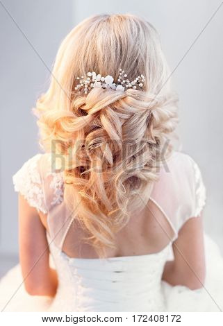 Bride in greek hair style. View of the curly hairstyle with comb decoration.