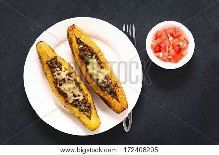 Baked ripe plantain stuffed with mincemeat olive green bell pepper and onion sprinkled with cheese a traditional dish in Central America called Canoa de Platano (Plantain Canoe) served with tomato and onion salad photographed overhead on slate with natura poster
