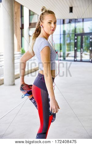 Portrait of sporty young woman stretching leg before running on footpath