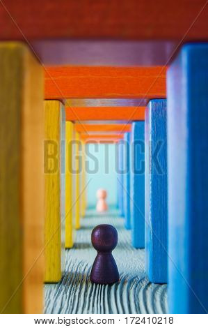 Abstract man into the colorful wooden corridor. Concept of success. Abstract man in a multicolored wooden tunnel. Two persons walk to the light in the end of the tunnel.