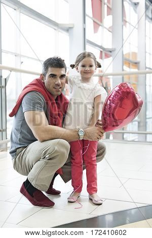 Father kneels with younger daughter holding balloon