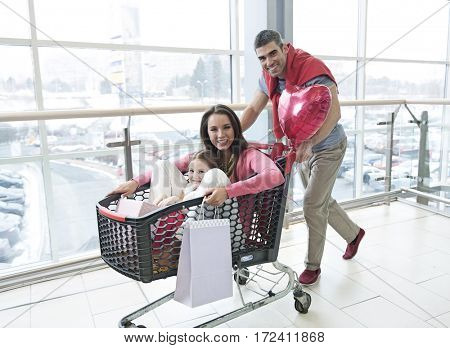 Father pushing mother and young daughter in shopping trolley