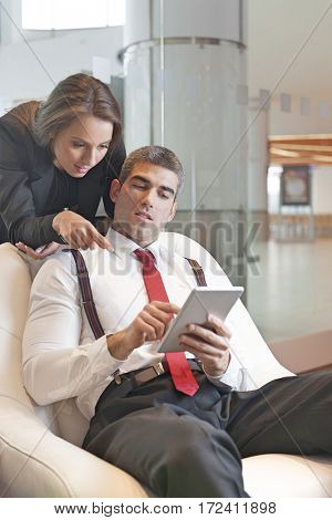 Businesswoman looking over male colleagues shoulder pointing at digital tablet