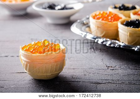 Black and red caviar tartlets, appetizer canapes on silver tray, horizontal