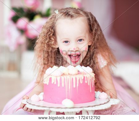 Laughing kid girl eating birthday cake with open mouth closeup in room. Looking at camera. Childhood.