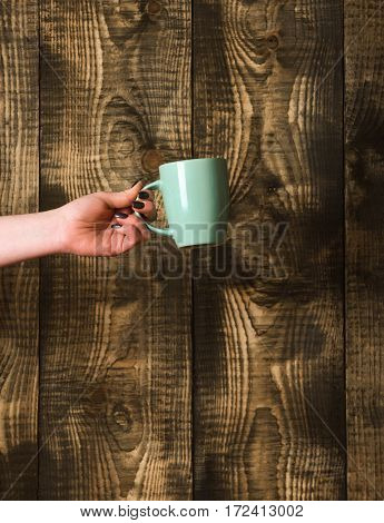 Blue Tea Or Coffee Cup In Hand On Wooden Background