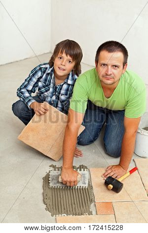 Father and son mounting ceramic floor tiles together in a new building