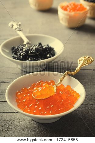 Black and red caviar tartlets, appetizer canapes in white bowls, vertical, toned