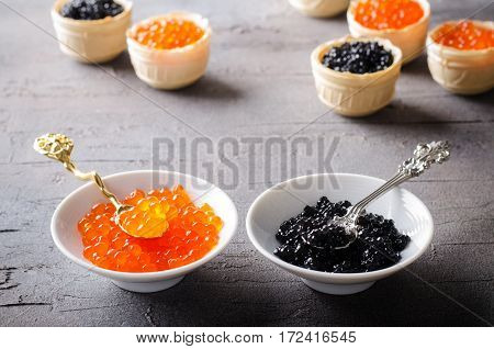 Black and red caviar tartlets, appetizer canapes in white bowls, horizontal