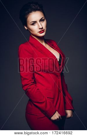 Attractive business woman. Portrait of a sexy young business lady in a red suit on a dark background.