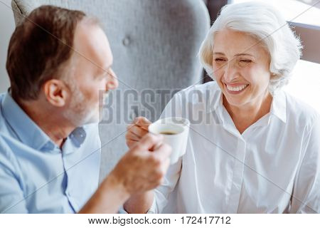 Warm atmosphere. Cheerful content smiling aged couple sitting at the table and drinking coffee while resting in the cafe