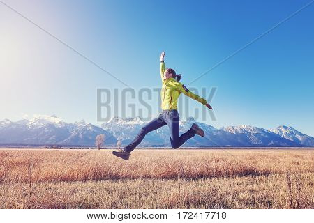 Happy Young Woman Jumping On A Mountain Meadow At Sunset.