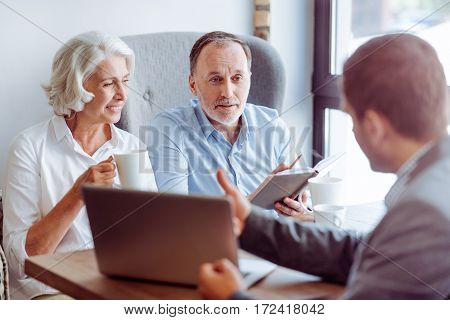 There are different options. Pleasant delighted aged couple sitting in the cafe and meeting with insurance agent while talking