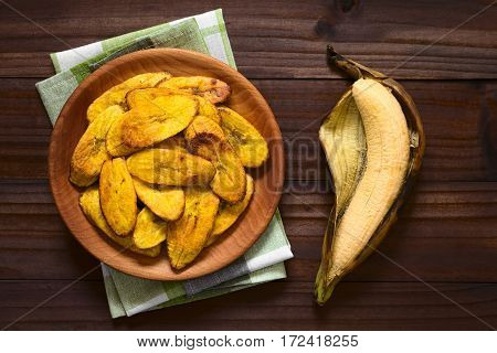 Fried slices of ripe plantains a traditional and popular snack and accompaniment in Central America and Northern South America photographed overhead on dark wood with natural light
