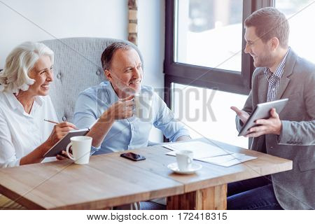 Important matters. Positive delighted senior couple talking with sales manager while meeting with him in the cafe