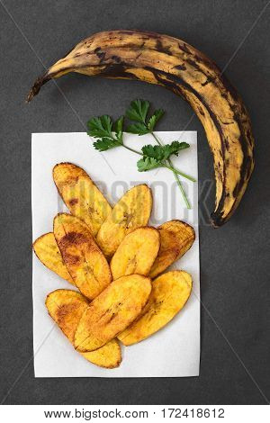 Fried slices of ripe plantains a traditional and popular snack and accompaniment in Central America and Northern South America photographed overhead on slate with natural light