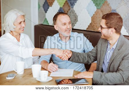 Deal. Cheerful pleasant smiling couple shaking hands with sales manager and meeting in the cafe