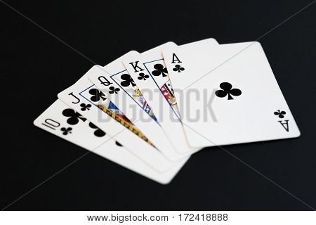 Royal Flush of clubs in poker cards game on a black background.