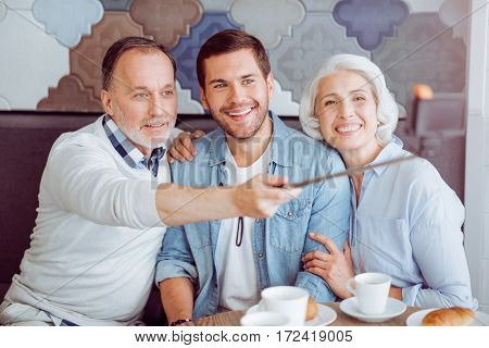 Catch the moment. Positive aged couple and thir grandson making selfies and having lunch while sitting in the cafe